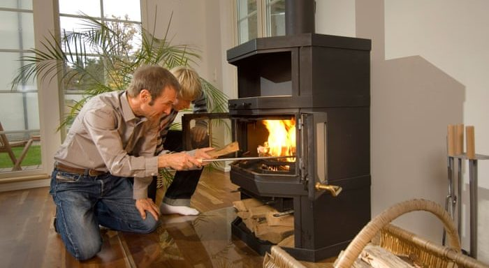 Father and son lighting wood burning stove