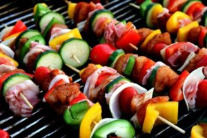 Skewering kebabs over a fire pit